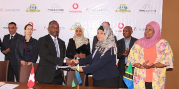 Ministry of Health Secretary, Asha Ali Abdulla (seated right) and Nathan Mulure, representative of Novartis (seated center) signing a contract to implement a ground breaking initiative that will provide medicine stock visibility.